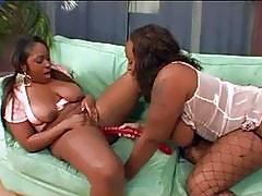 Sexy black lesbians share a toy that penetrates ebony pussy
